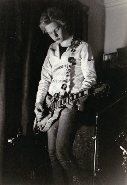 Peter Timusk playing a six string guitar in 1979 at a Rock against racism event. Spot light playing lead guitar.